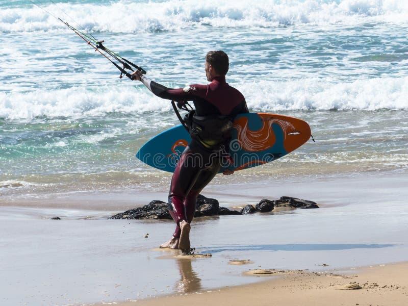 Persona que practica surf de la cometa en la playa que entra en el mar foto de archivo