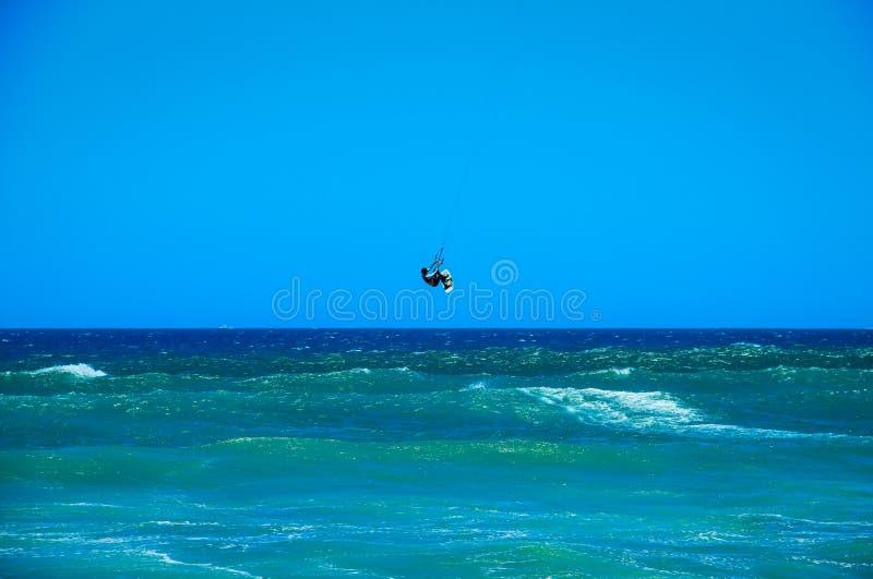 Persona que practica surf de la cometa que salta del agua fotografía de archivo
