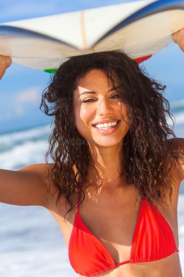 Persona que practica surf de la muchacha de la mujer del bikini y playa hermosas de la tabla hawaiana fotografía de archivo libre de regalías