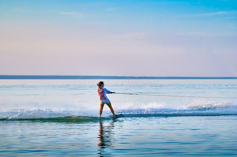 Persona que practica surf de la mujer con los rollos rojos del pelo en el tablero en una superficie plana del agua fotografía de archivo