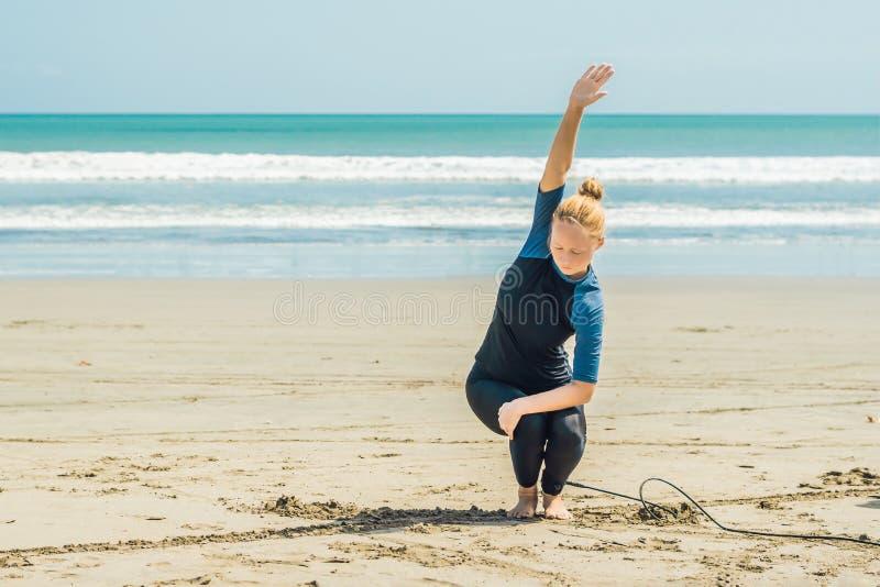 Persona que practica surf de la mujer joven que calienta en la playa antes de practicar surf foto de archivo