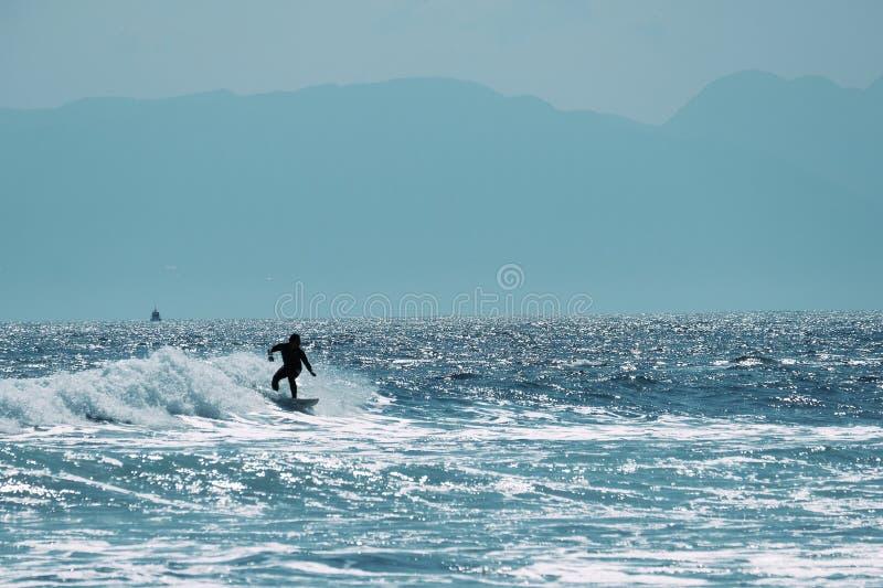 Persona que practica surf de sexo masculino en el océano, concepto del fondo del verano imagen de archivo