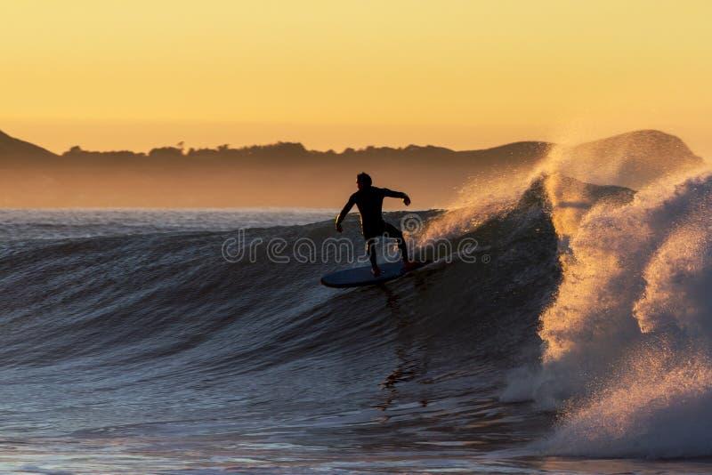 Persona que practica surf del amanecer fotografía de archivo libre de regalías