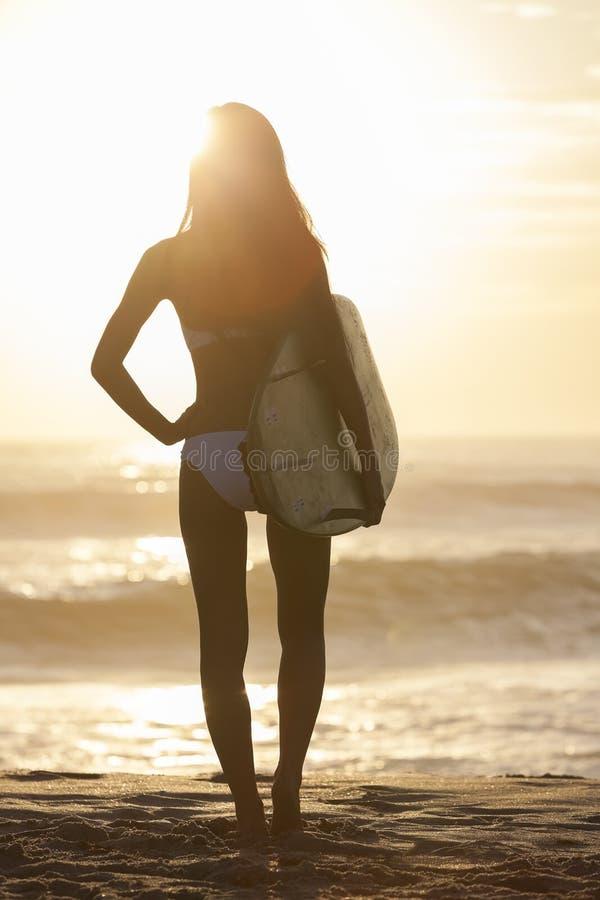 Persona que practica surf del bikiní de la mujer y playa de la puesta del sol de la tabla hawaiana imagen de archivo