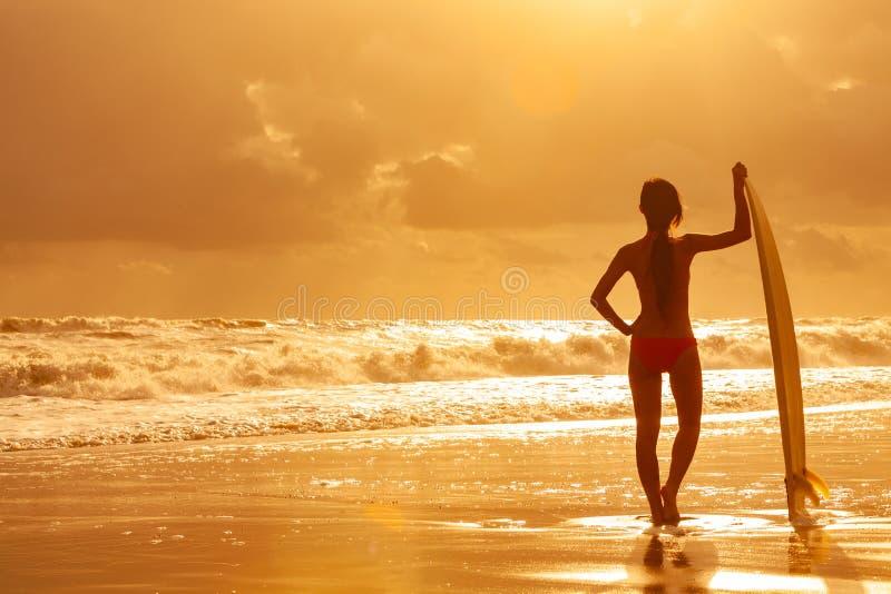 Persona que practica surf del bikin? de la mujer y playa de la puesta del sol de la tabla hawaiana foto de archivo