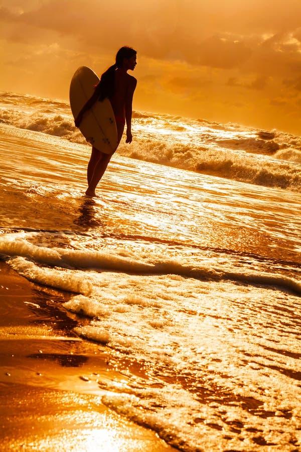 Persona que practica surf del bikin? de la mujer y playa de la puesta del sol de la tabla hawaiana fotografía de archivo