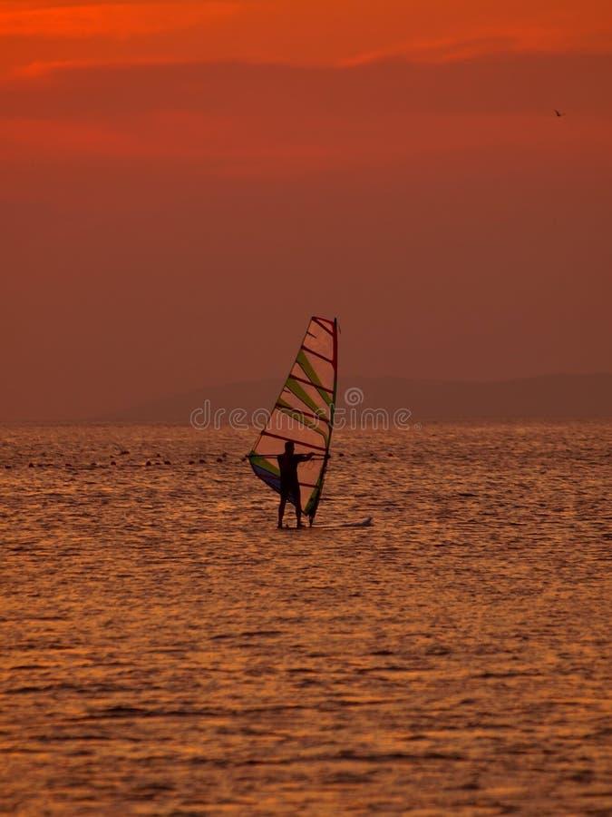 Persona que practica surf del viento en la puesta del sol fotografía de archivo libre de regalías
