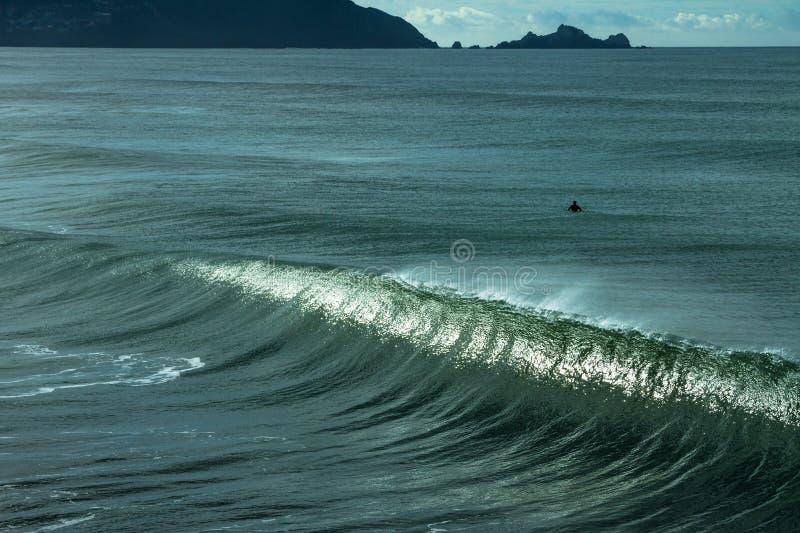 Persona que practica surf en el océano que espera la onda perfecta imagenes de archivo