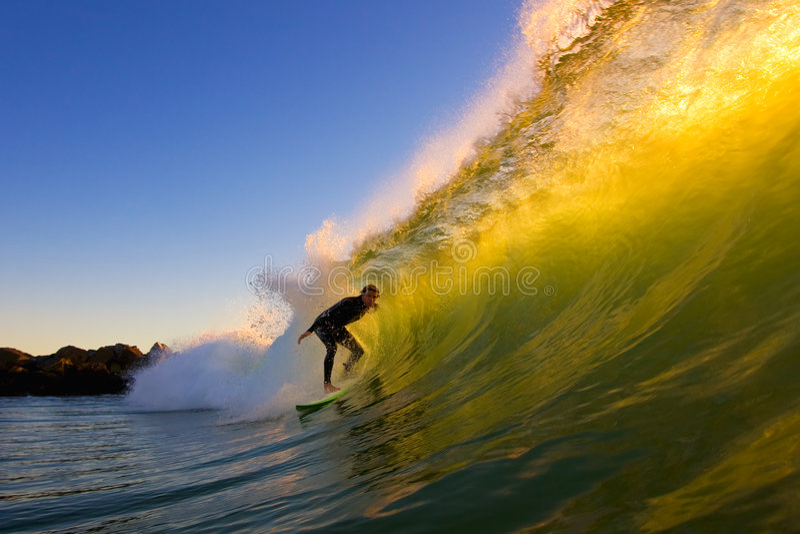 Persona que practica surf en el tubo en la puesta del sol foto de archivo libre de regalías
