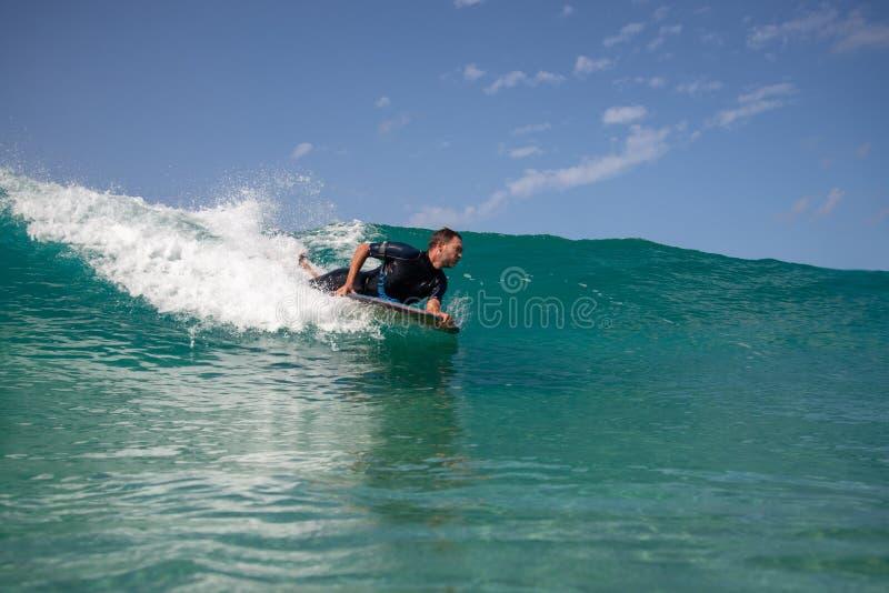 Persona que practica surf en la acción en la onda imagenes de archivo