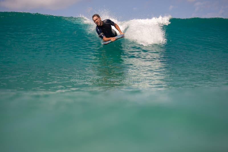 Persona que practica surf en la acción en la onda foto de archivo