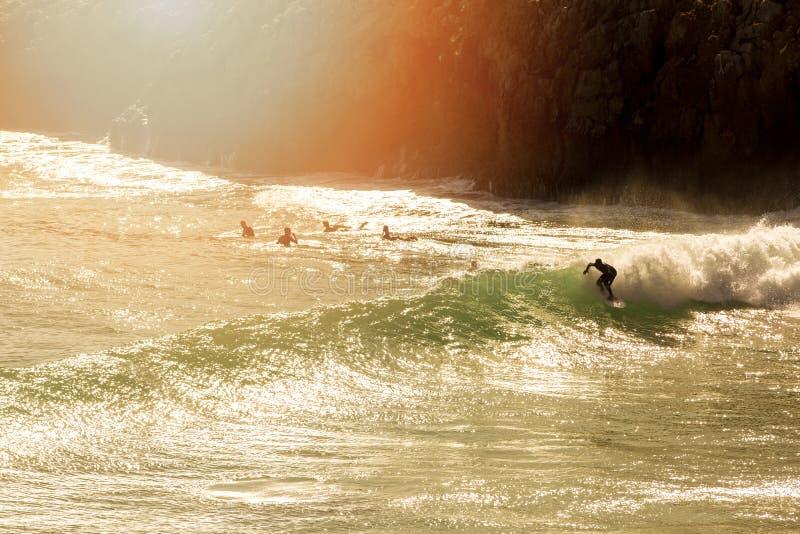 Persona que practica surf en la onda en la puesta del sol imagen de archivo libre de regalías
