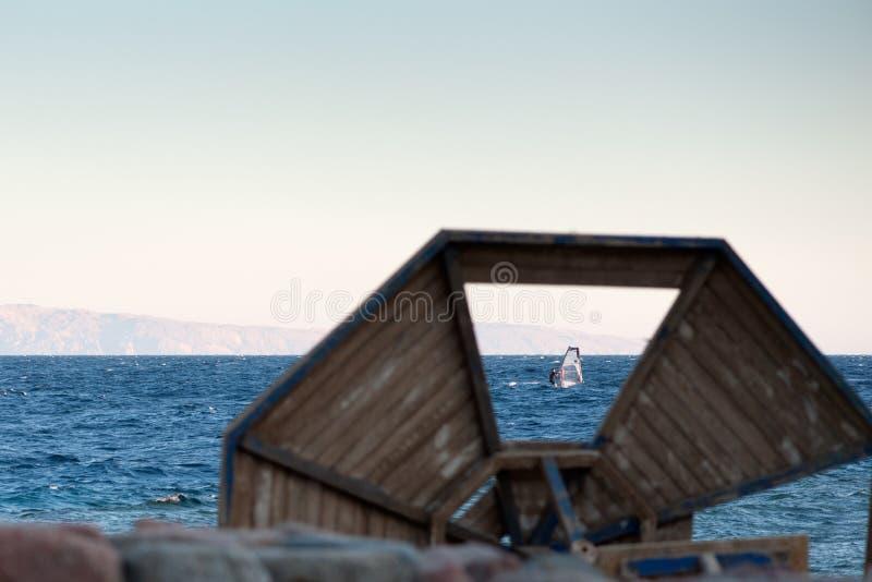 Persona que practica surf en la opinión del Mar Rojo a través de un parasol de madera quebrado que miente en la orilla fotos de archivo libres de regalías