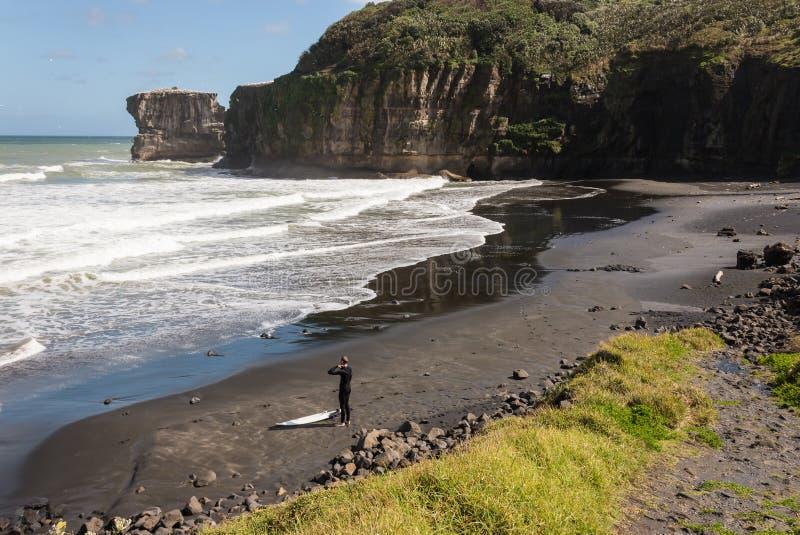 Persona que practica surf en la playa en Maori Bay fotos de archivo
