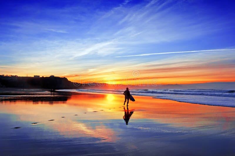 Persona que practica surf en playa en la puesta del sol fotos de archivo