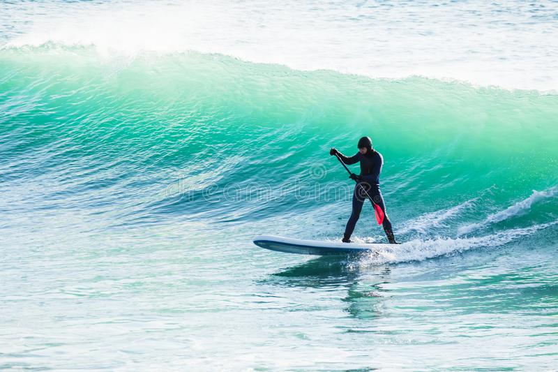 Persona que practica surf en tablero del sorbo en olas oceánicas Levántese el embarque de la paleta en el mar fotografía de archivo libre de regalías