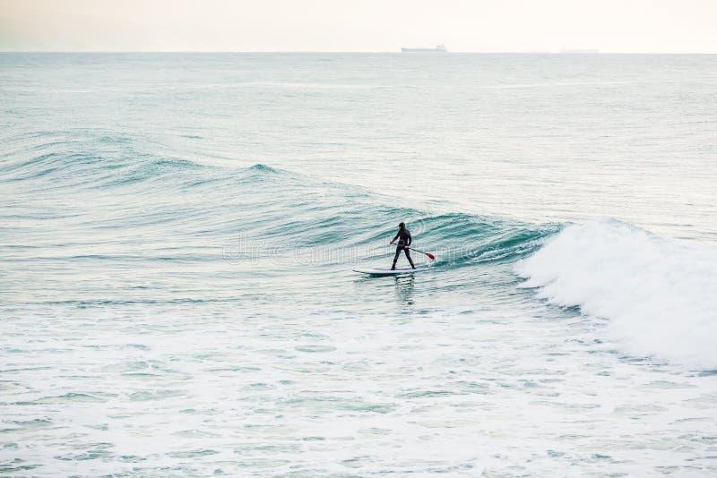 Persona que practica surf en tablero del sorbo en olas oceánicas Levántese el embarque de la paleta en el océano fotografía de archivo libre de regalías