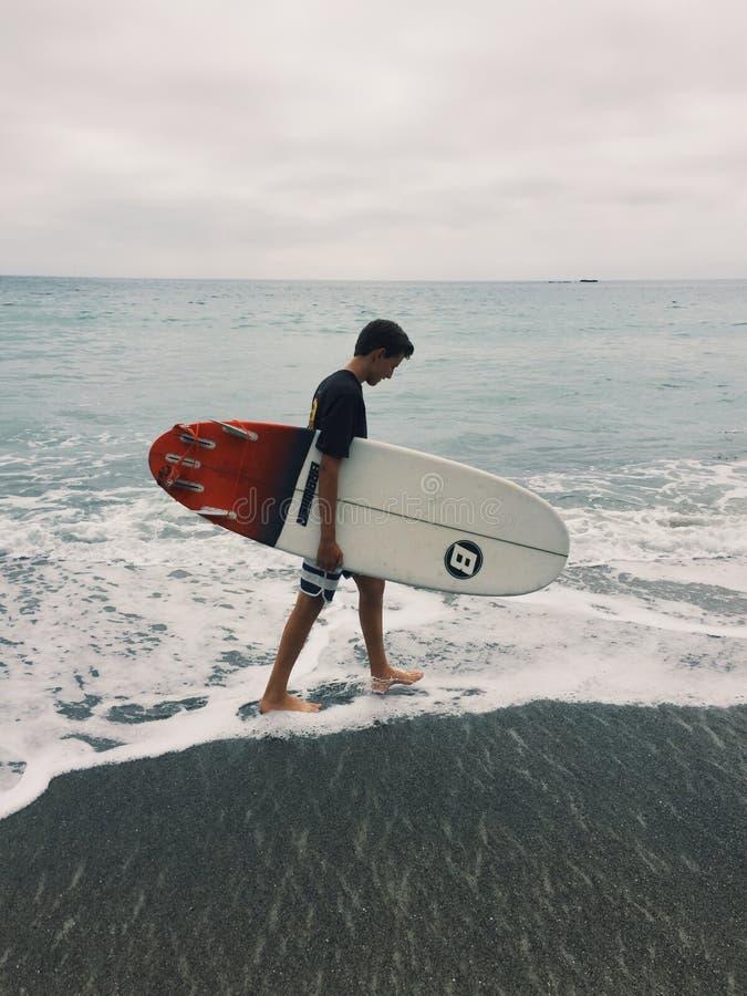 Persona que practica surf joven que camina en la playa imagen de archivo