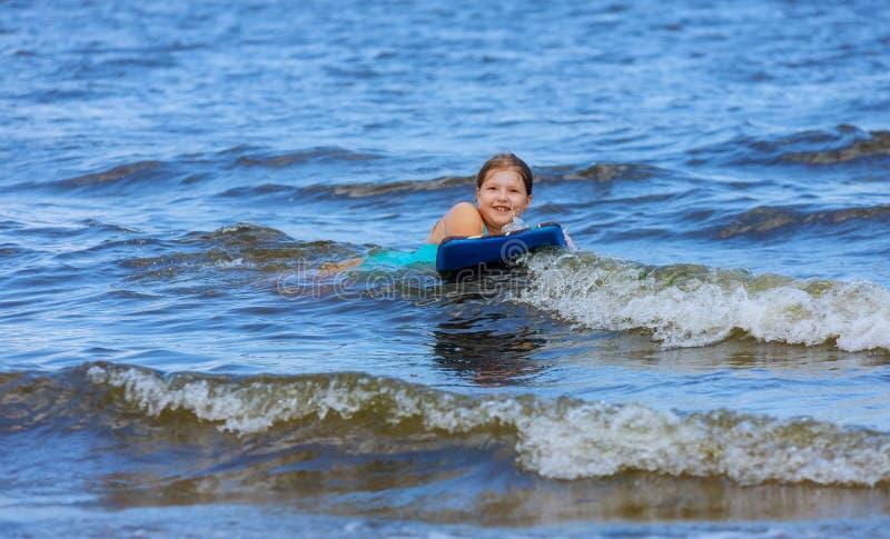 Persona que practica surf joven del pequeño bebé adorable con bodyboard una diversión en pequeñas olas oceánicas imagen de archivo libre de regalías