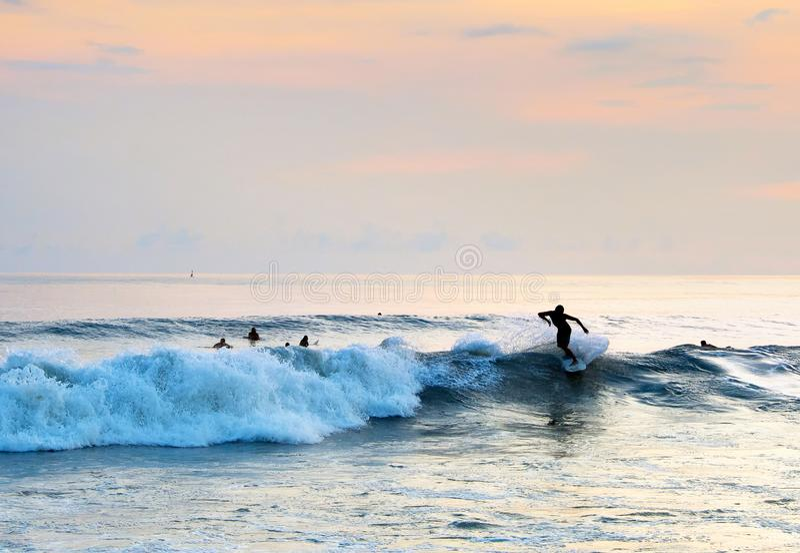 Persona que practica surf que monta una onda bali fotos de archivo libres de regalías