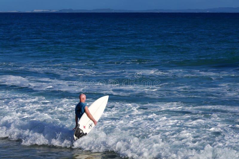 Persona que practica surf que entra en el océano con su tablero foto de archivo