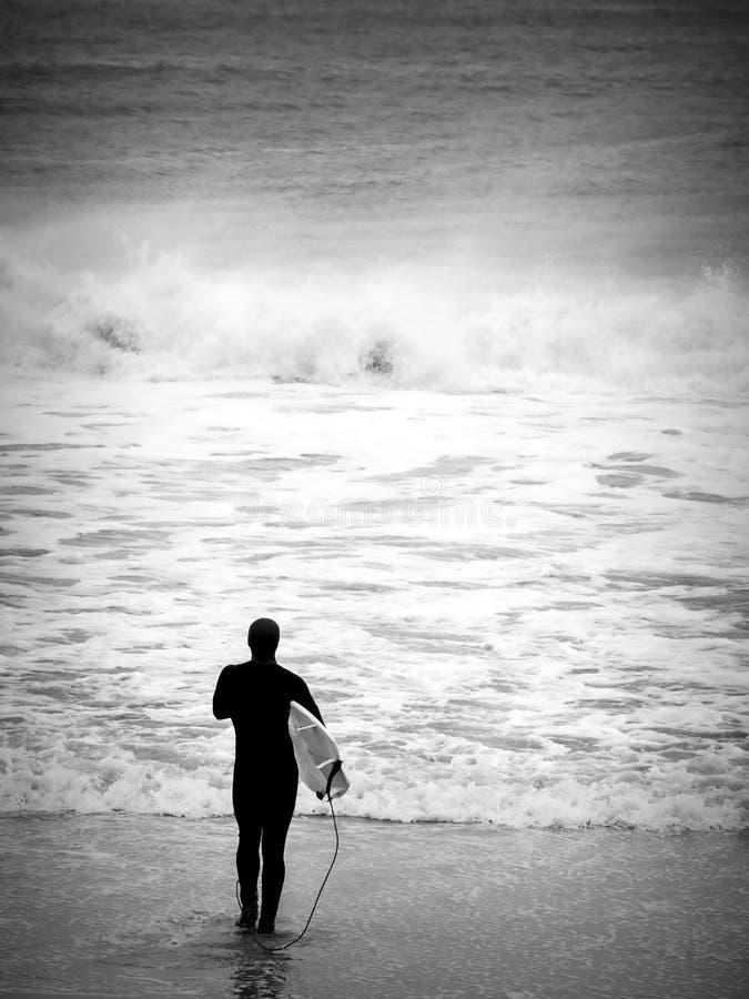 Persona que practica surf que espera el grande imagen de archivo libre de regalías
