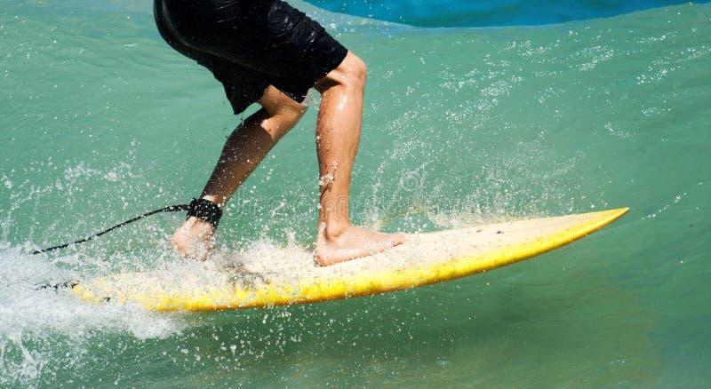 Persona que practica surf que monta una onda fotografía de archivo