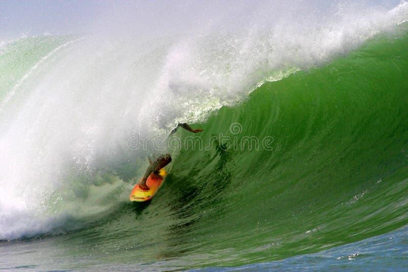 Persona que practica surf que practica surf una onda de océano fotos de archivo libres de regalías