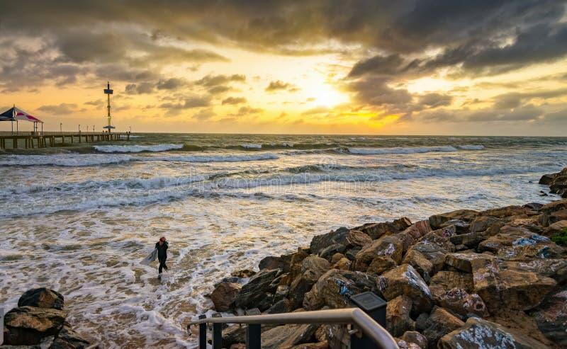 Persona que practica surf que sale del agua en la puesta del sol fotos de archivo libres de regalías