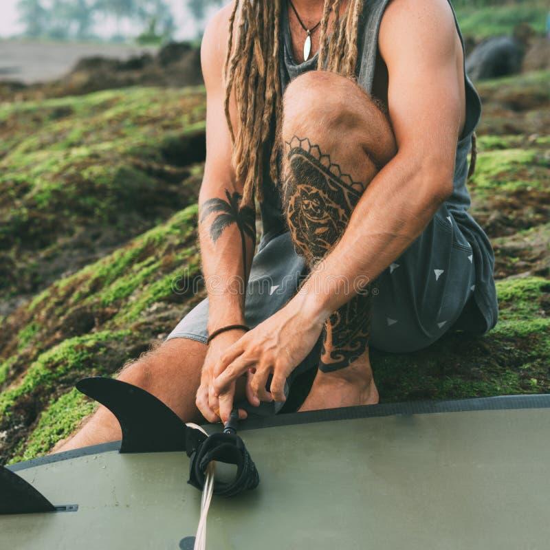 Persona que practica surf que se sienta con los tatuajes, dreadlocks cerca para arriba fotos de archivo