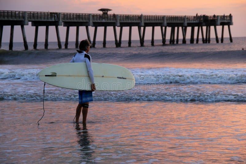Persona que practica surf solitaria que se coloca en la resaca en una mañana magnífica, playa de Jacksonville, la Florida, 2015 imagenes de archivo