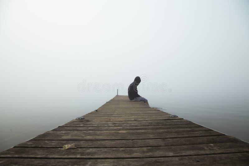Persona que se sienta el madrugada del muelle con niebla en el cielo imagen de archivo