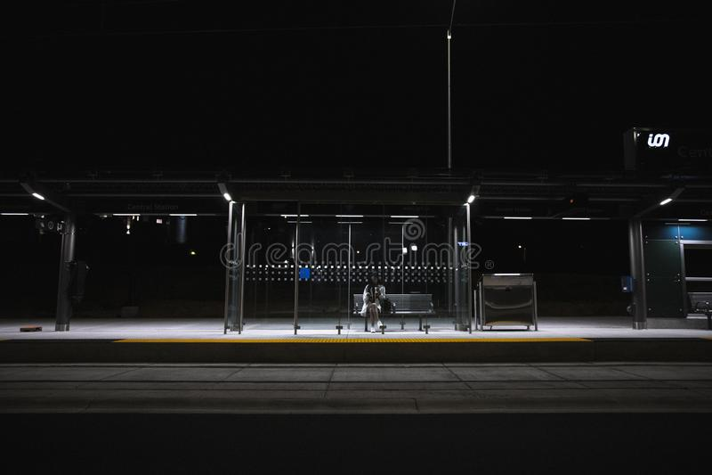 Persona que se sienta en la parada de autobús todo solamente atrasada en la noche foto de archivo