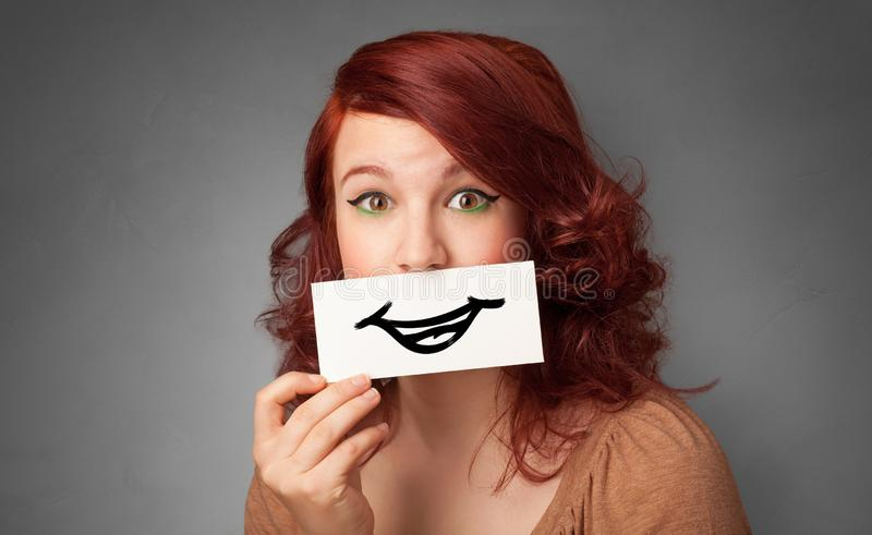 Persona que sostiene delante de su boca una tarjeta fotos de archivo