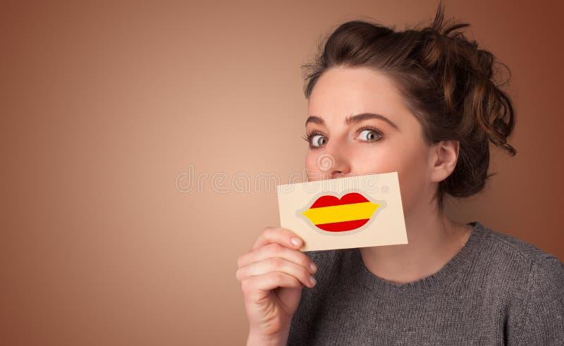 Persona que sostiene la tarjeta de la bandera de España imagen de archivo