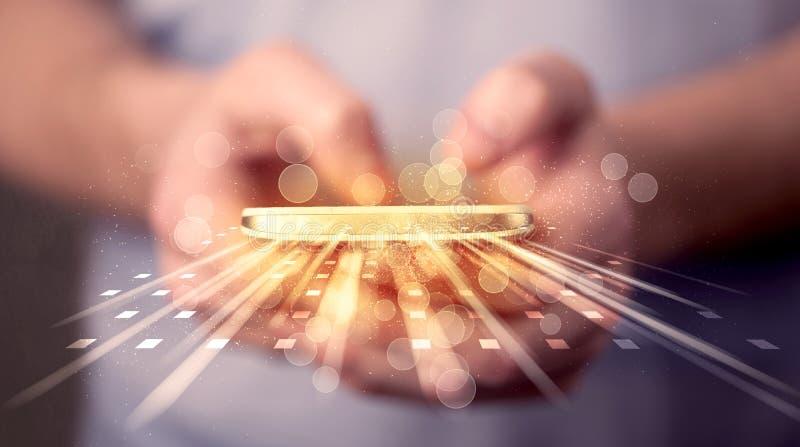 Persona que sostiene smarthphone con usos de la luz de la tecnología fotos de archivo libres de regalías