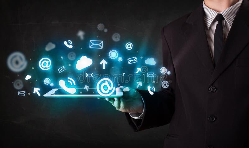 Persona que sostiene una tableta con los iconos y los símbolos azules de la tecnología imagen de archivo