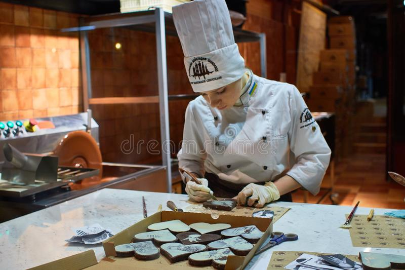 Persona que trabaja dentro de la fábrica hecha en casa del chocolate de Lviv fotografía de archivo