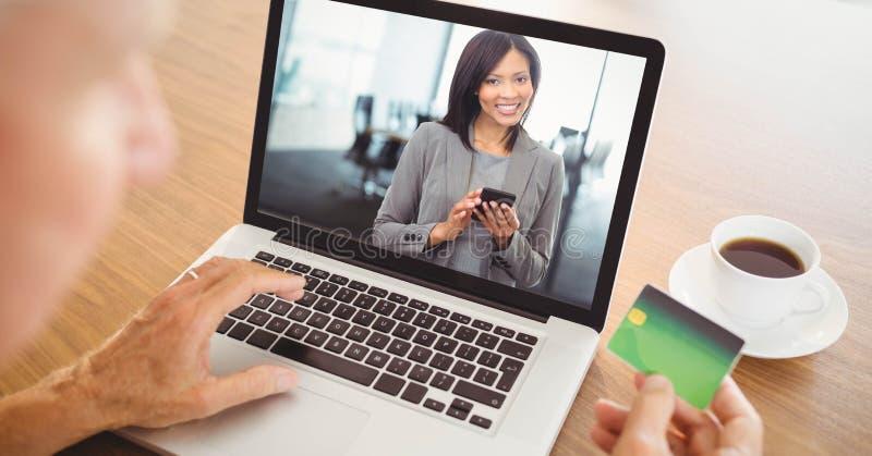 Persona que usa la tarjeta mientras que comunicación video con la empresaria en el ordenador portátil imágenes de archivo libres de regalías