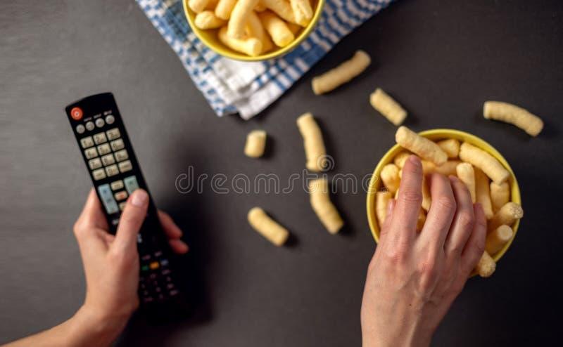 Persona que ve una TV y comer los bocados, soplos del maíz fotografía de archivo libre de regalías