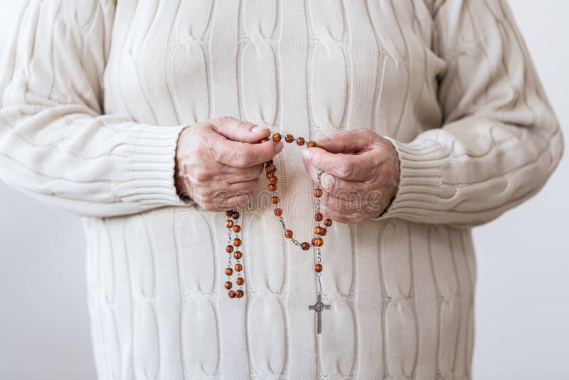 Persona religiosa con el rosario rojo fotos de archivo