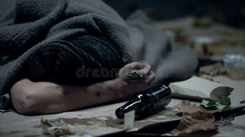 Persona sin hogar borracha que duerme en la calle de la ciudad, abuso de alcohol, problema social imagen de archivo libre de regalías