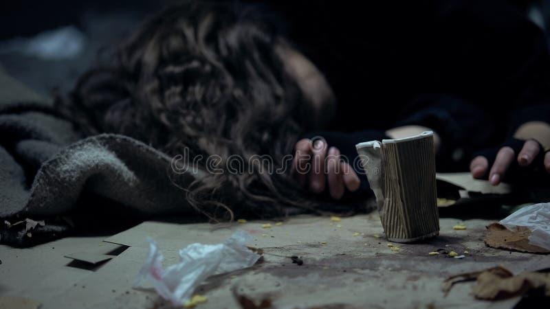 Persona sin hogar borracha que duerme en la calle de la ciudad, taza próxima, problema social del mendigo fotos de archivo