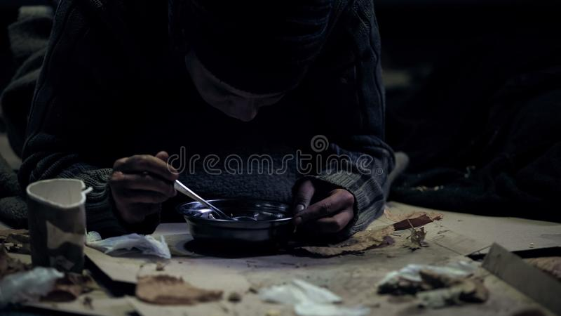 Persona sin hogar codicioso que come la sopa del cuenco de acero, refugio sucio, hambre foto de archivo libre de regalías