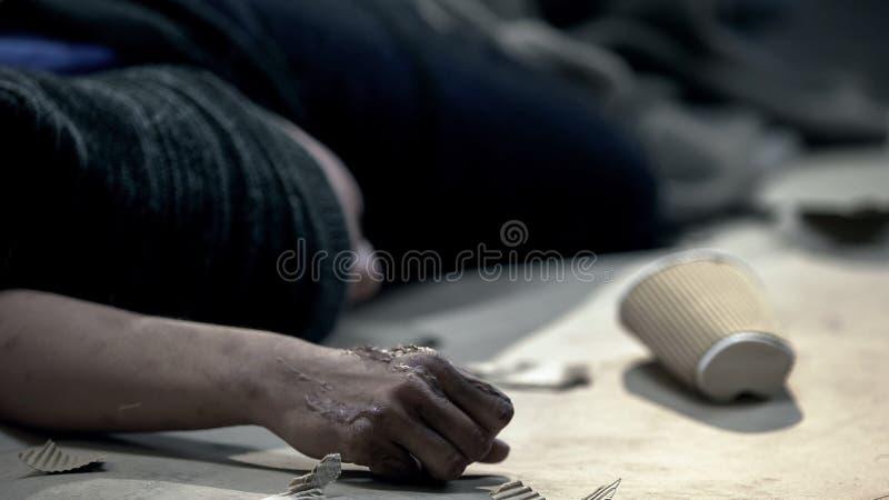 Persona sin hogar con la enfermedad de la piel que duerme en la calle sucia, ciudad fr?a de la noche fotos de archivo libres de regalías
