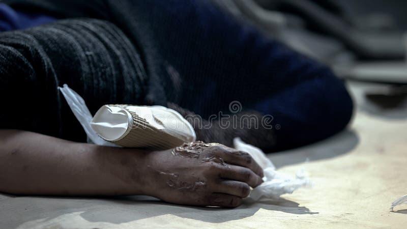 Persona sin hogar con las quemaduras de la piel que duerme en la calle sucia, cubriendo de frío fotos de archivo
