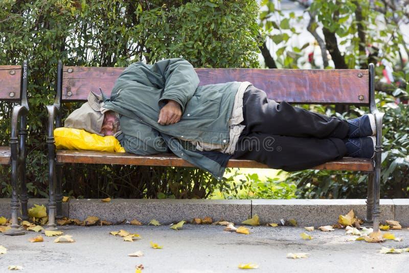 Persona sin hogar en un banco fotografía de archivo libre de regalías