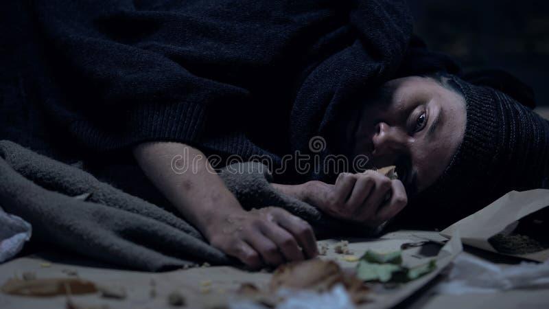 Persona sin hogar hambrienta enferma que miente en la calle y que come el pedazo pasado de orts imagenes de archivo