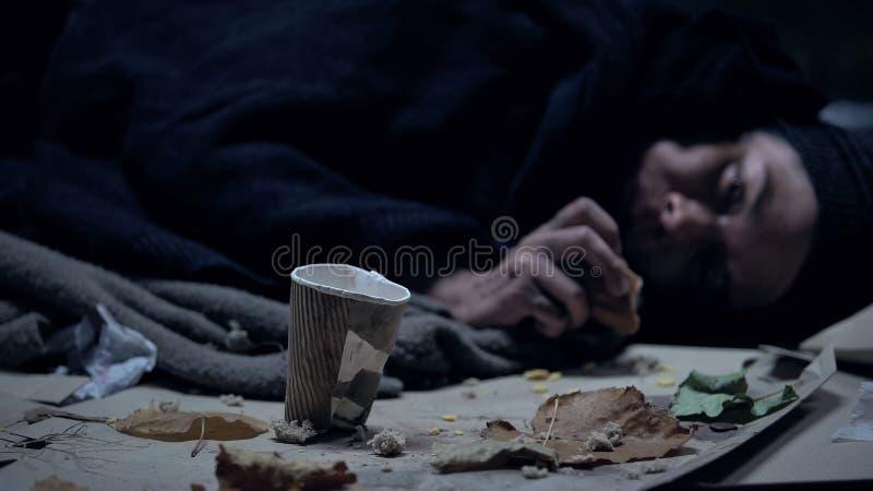 Persona sin hogar que miente en la calle que come el pedazo de pan pasado, taza de papel cerca imagen de archivo libre de regalías