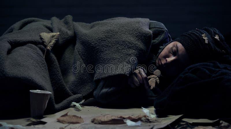 Persona sin hogar sola con la figura de papel que miente en hogar y la familia perdidos de la calle fotos de archivo